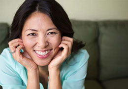 Middle-aged Asian women sitting on a couch and smiling